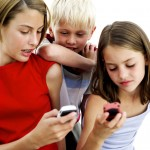 Young Girls Operating Cell Phones with a Young Boy (10-14) Standing Behind Them
